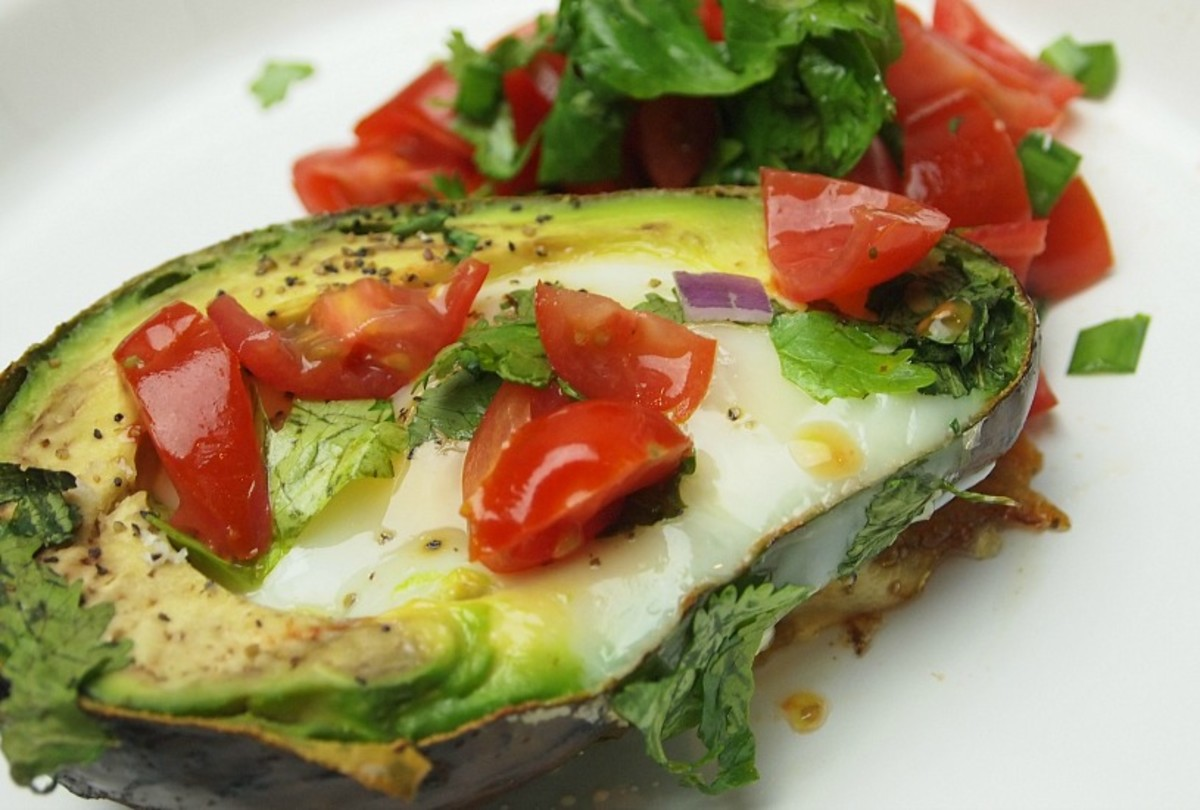 Avocado Baked Eggs are topped with tomatoes and cilantro and sprinkling of salt and pepper, the perfect low carb breakfast.