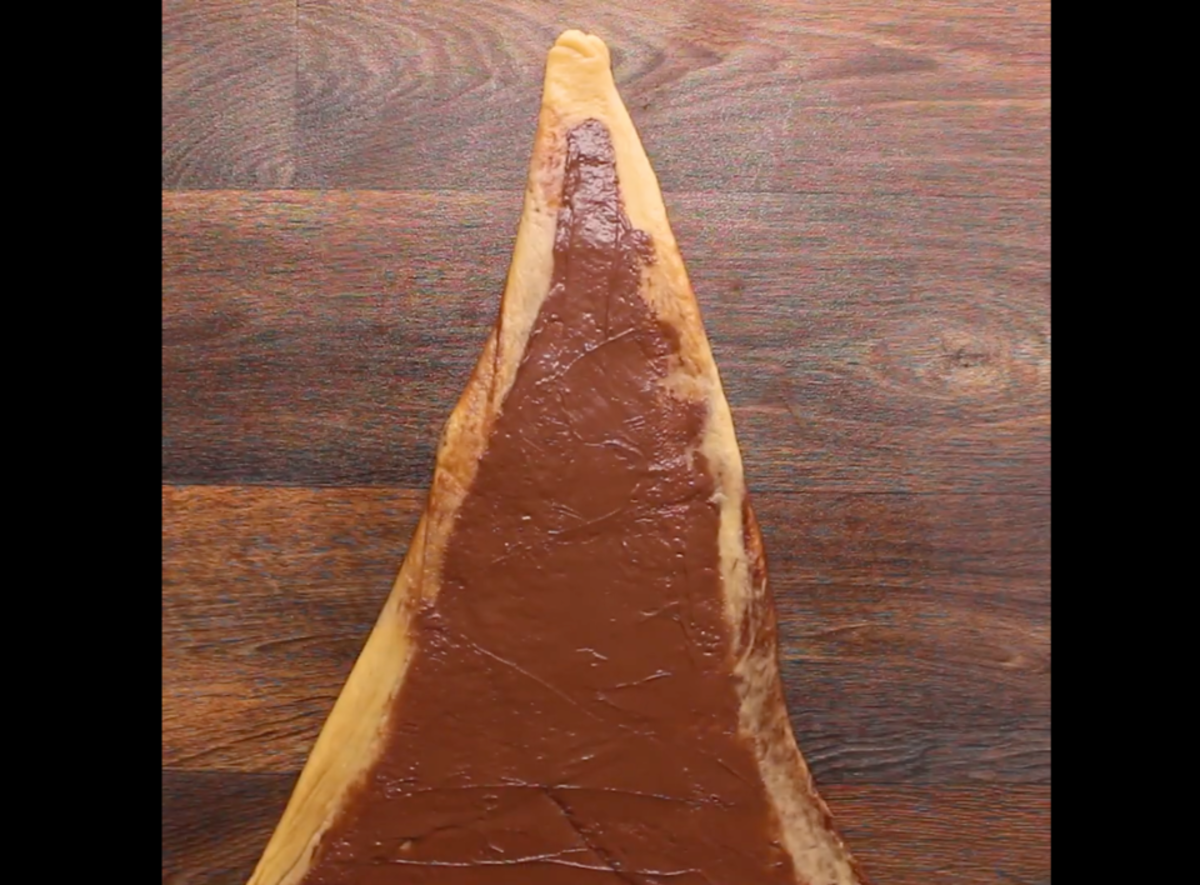 The third layer of chocolate spread onto the rectangle with the corners folded in, then rolled.