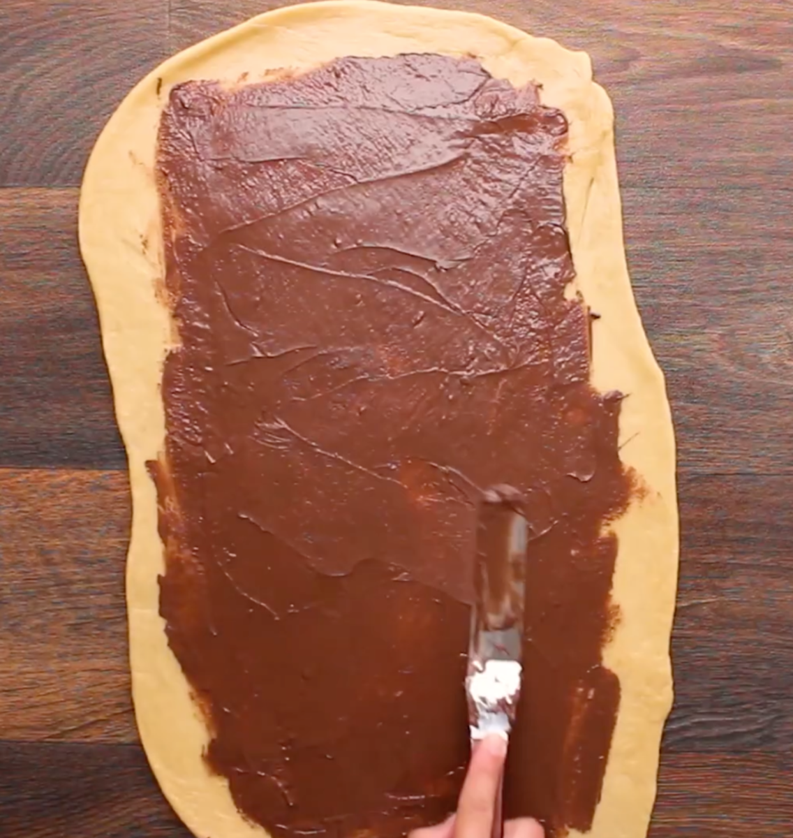 Spreading the first layer of chocolate on the dough rectangle.